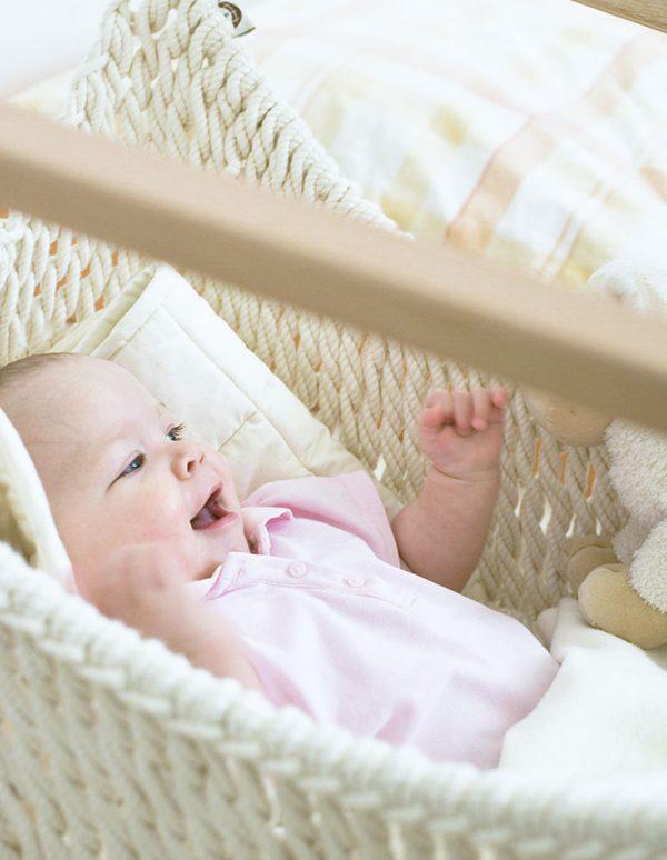 Ein Baby im Babyschwinger neben dem Elternbett