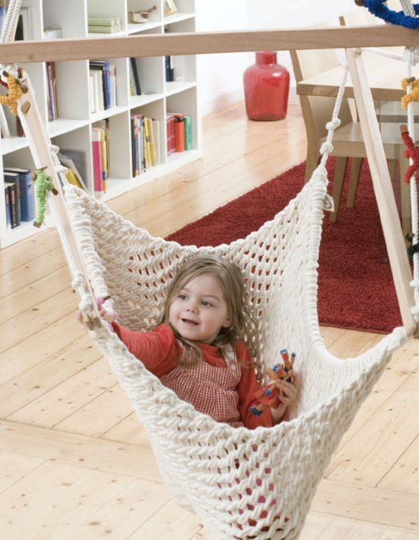 Ein Kind spielt im Babyschwinger